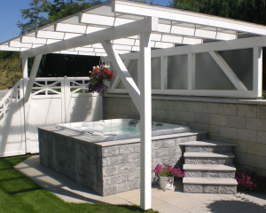 Outdoor hot tub installed underneath a white pergola.